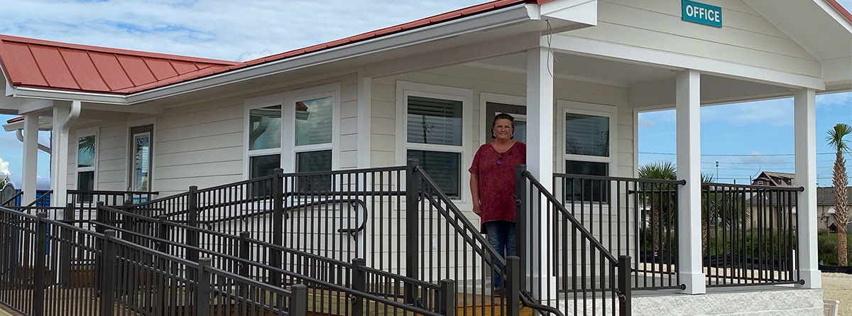 Image of Tangie Horton standing on the front porch of our new RV Park Office.